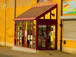 Vue de l'entrée vitrée, en décrochage par rapport à la façade de briques jaunes.